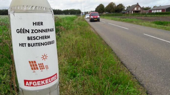 Langs de Vroenhoutseweg zijn demonstratiepamfletten aangebracht: 'Hier géén zonnepark, bescherm het buitengebied.'