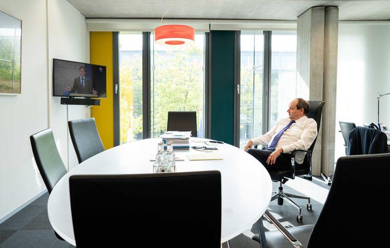 Staatssecretaris Hans Vijlbrief (Financiën) volgt de Algemene Beschouwingen vanuit zijn werkkamer op het Ministerie van Financiën. Beeld ANP