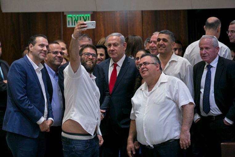 Een parlementslid neemt in juli 2018 een foto met premier Netanyahu, nadat een omstreden wet is aanvaard die bepaalt dat Israël de staat is van het Joodse volk.  Beeld AP