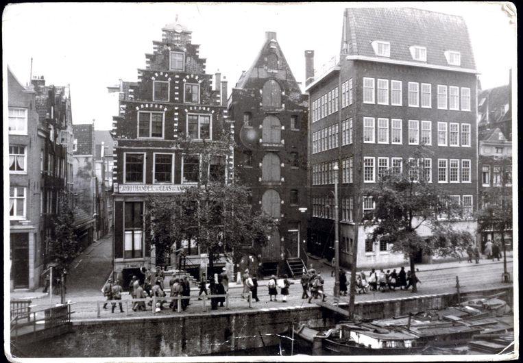 Een foto van een razzia van mei 1943 op de Geldersekade. Rechts wordt een deur ingetrapt. Beeld Herman J. Wijnne, Anne Frank Stichting