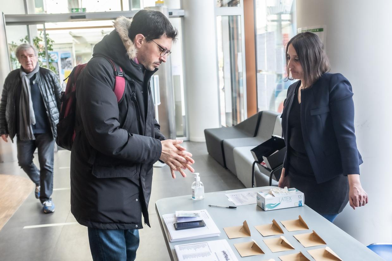 Een man wast zijn handen met desinfecterende gel voordat hij een stem gaat uitbrengen in een stembureau in Parijs. Beeld Joris Van Gennip