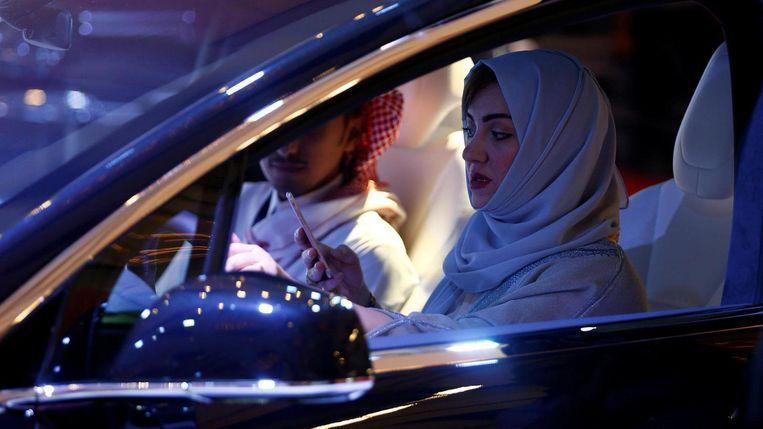 Een vrouw met hoofddoek zit achter het stuur in Saoedi-Arabië. Beeld Reuters