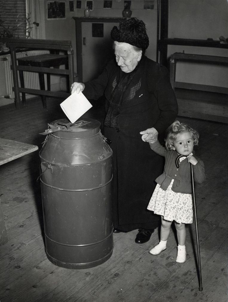 De 101-jarige overgrootmoeder mevrouw C. Krouwels-Traksel uit Haarlem doet haar stembiljet in de stembus bij de verkiezingen van 25 juni 1952, terwijl haar achterkleindochter Tineke haar wandelstok vasthoudt. Beeld Nationaal Archief/Collectie Spaarnestad/C. de Boer