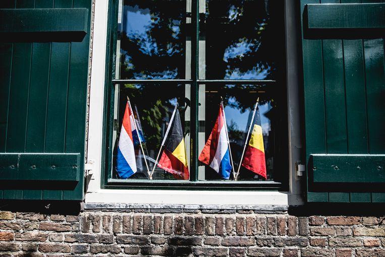 Belgische en Nederlandse vlaggen in het raam van het gemeentehuis van Baarle-Nassau, waarin ook het kantoor van Toerisme Baarle zetelt.  Beeld Aurélie Geurts