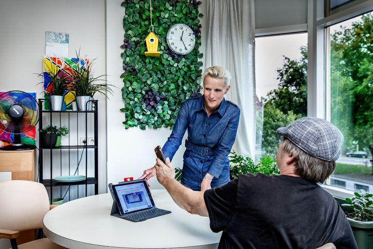 Psychologe Roeline Biemond leert korsakovpatiënt Victor Dubois via een appje op haar laptop om te gaan met een smartphone. Beeld Jean-Pierre Jans