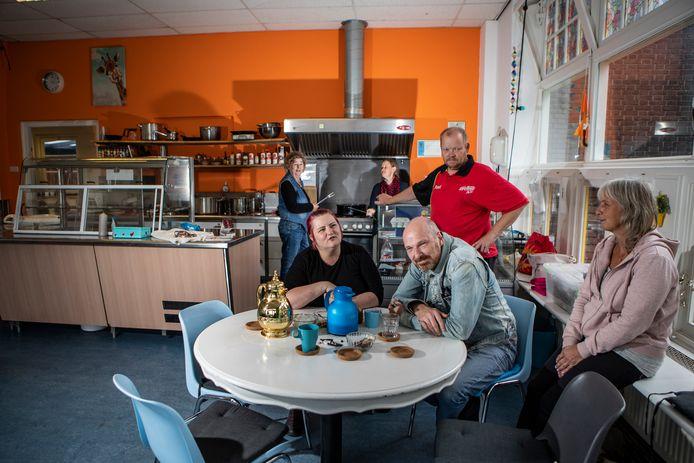 In de huiskamer kookt Alie wekelijks. De buurtgenoten zijn verdrietig dat ze hun goede werk niet door kunnen zetten. Van links naar rechts: Alie, Lotte, Trijntje, Daan, Geo en Saskia.