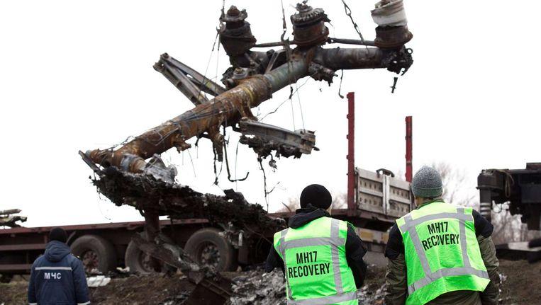 Het Nederlandse repatriëringsteam kijkt toe terwijl delen het vliegtuig op een truck getakeld worden, beeld van november 2014. Beeld afp