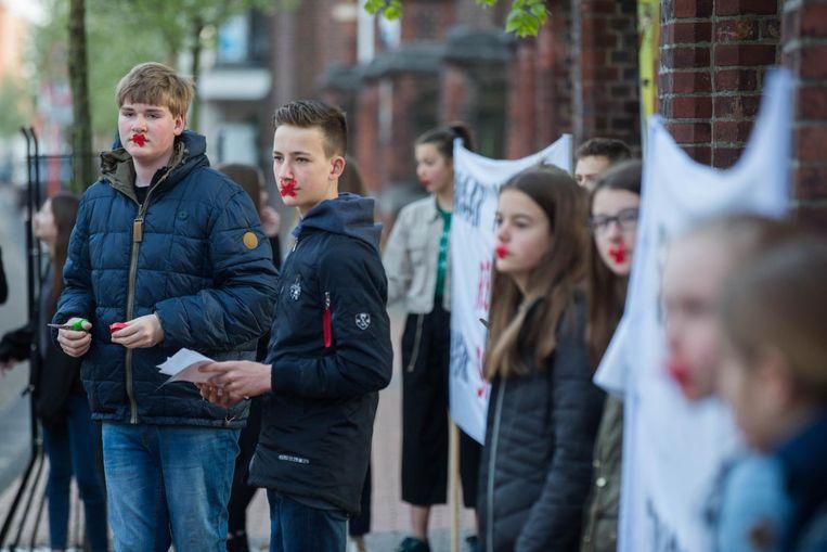 Aan het Sint-Hubertuscollege voeren leerlingen een stil protest met tape over hun mond.