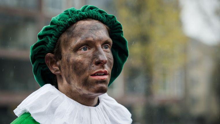 Een Zwarte Piet (roetpiet of schoorsteenpiet) met slechts enkele roetvegen op het gezicht tijdens de intocht van Sinterklaas. Beeld anp