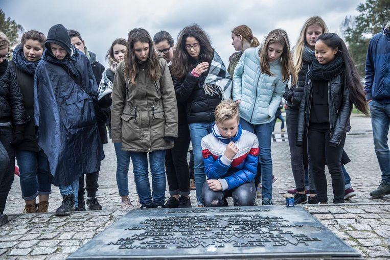 Schoolklas bij de gedenkplaat voor Nederlandse slachtoffers in Auschwitz. Beeld Marlena Waldthausen