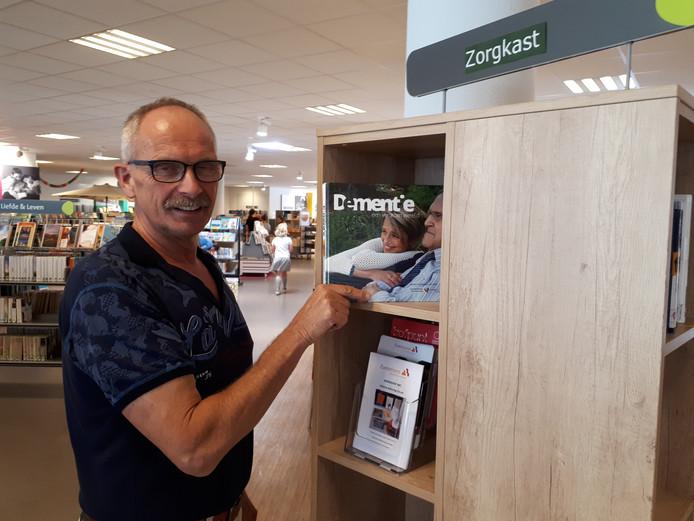 Bibliotheekmedewerker Henk van de Maat vult de mantelzorgkast met boeken.