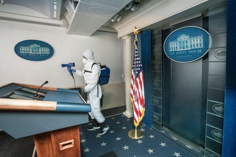 Een schoonmaker desinfecteert de zaal van het Witte Huis waarin persconferenties worden gehouden. Beeld EPA/KEN CEDENO / POOL