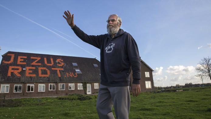 Joop van Ooijen voor zijn woonboerderij met op het dak zijn religieuze boodschap.