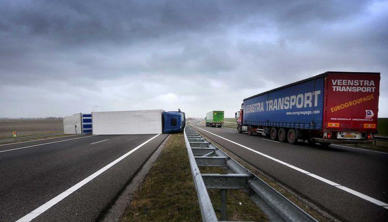 Een omgewaaide vrachtauto ligt dwars over de weg op de N31 bij Harlingen. Beeld anp