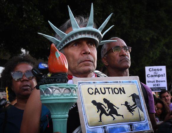 Een man draagt een kostuum van het Vrijheidsbeeld tijdens een protest tegen Trumps migrantenbeleid.