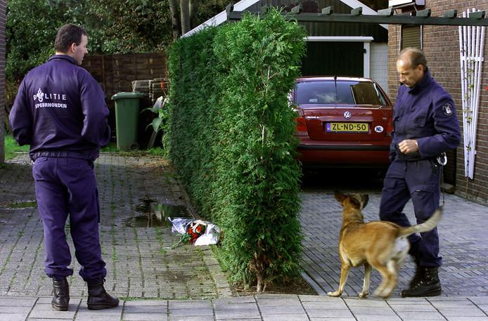 Terwijl bloemen voor slachtoffer Tonny ter Horst op de plek liggen waar  hij is overleden, zoeken agenten met speurhonden naar eventuele kogelhulzen.