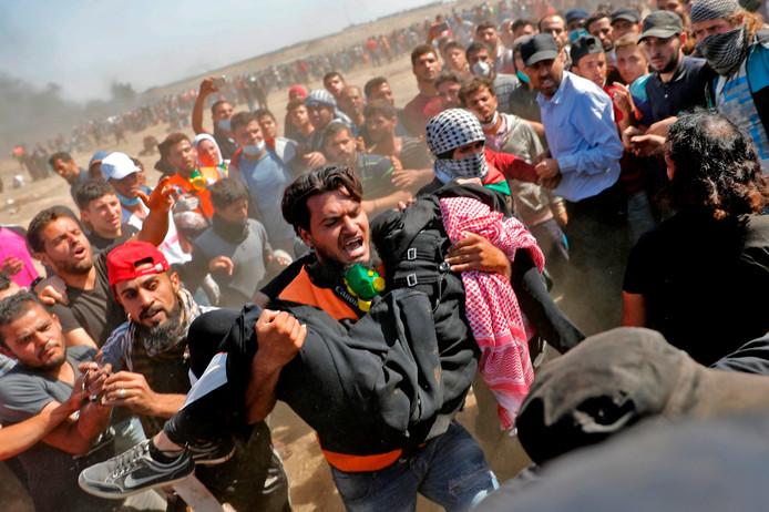 Een Palestijn draagt een gewonde demonstrant in het grensgebied tussen Israël en de Gazastrook. Ruim 40 personen zijn vandaag om het leven gekomen door confrontaties met het Israëlische leger. Foto Thomas Coex