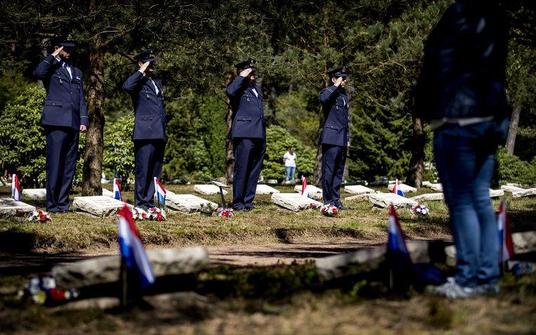 De dodenherdenking afgelopen 4 mei op het Nationaal Ereveld in Loenen. Vrijwilligers en betrokken staan bij de graven van oorlogsslachtoffers.  Beeld ANP