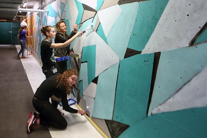 Leerlingen van 't Rijks zijn volop in de weer om de muren in de grauwe fietskelder te voorzien van een vrolijke kleur.