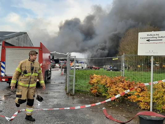 Brandweer aan het werk om het vuur in Caravanstalling Oeffelt onder controle te krijgen.