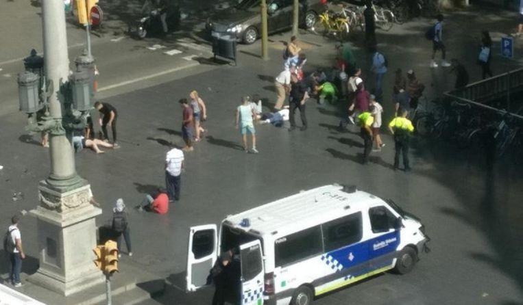 Voetgangers liggen op de grond vlak nadat een wit busje een stoep op is gereden. Beeld Twitter