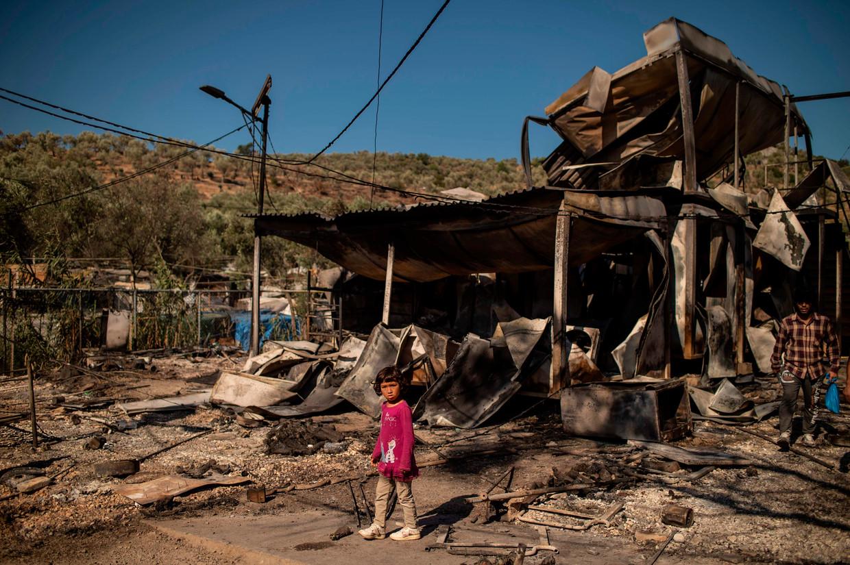 Een meisje staat bij de overblijfselen van vluchtelingenkamp Moria, dat vannacht in vlammen opging.