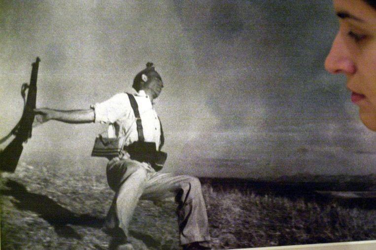 Vrouw bekijkt The falling soldier van Robert Cappa op een tentoonstelling. (EPA) Beeld null