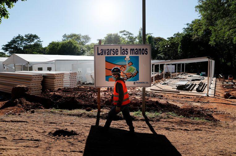 Achter een ziekenhuis in de stad Asunscion in Paraguay wordt een nieuw gebouw neergezet om meer coronapatiënten te kunnen opvangen en behandelen. Een bord spoort voorbijgangers aan om hun handen te wassen. Beeld AP