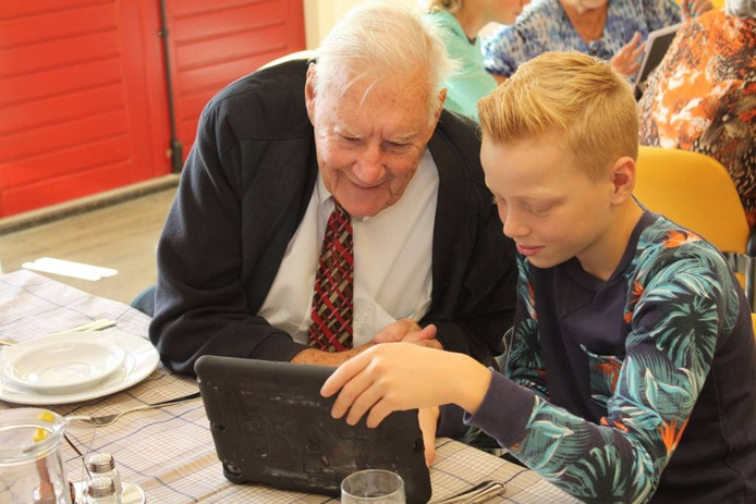 Op de iPad laten leerlingen aan de ouderen zien hoe het schoolleven op Groevenbeek eruit ziet.