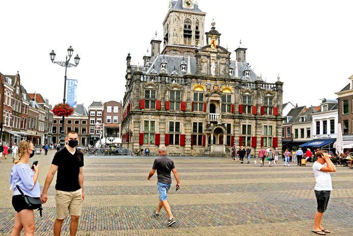Een stel toeristen met mondkapje op voor het Stadhuis van Delft op een rustige Markt.