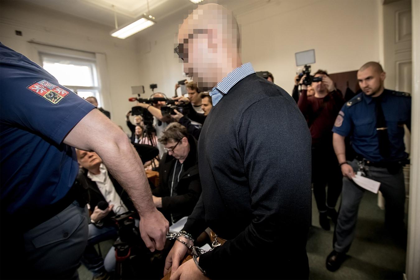 Armin N. wordt door agenten geboeid de rechtszaal ingeleid.