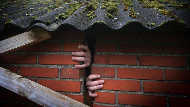 Handen zijn zichtbaar door een scheur in de muur van een woning in het Groningse Bedum. Beeld null