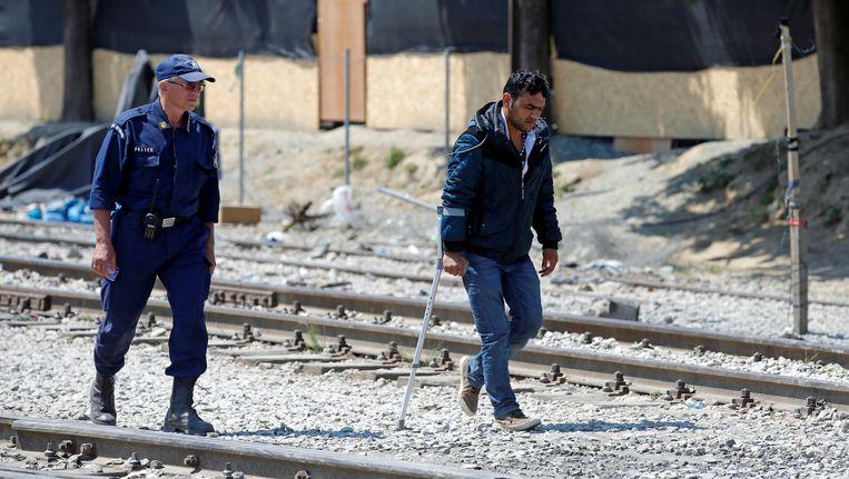 Een Griekse agent begeleidt een vluchteling bij Idomeni. Beeld reuters