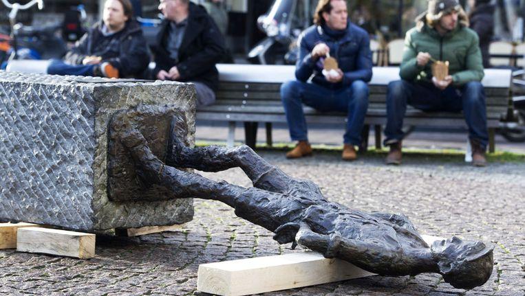 Een vrachtwagen heeft per ongeluk het standbeeld Het Lieverdje op het Spui in Amsterdam omvergereden. Beeld ANP