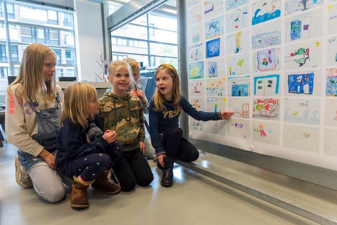 Amélie van Ostade (rechts) legt haar tekening uit bij de expositie van tekeningen voor het kinderboek 'De verlegen vis Ferdinand' in de bibliotheek in de Witte Dame.