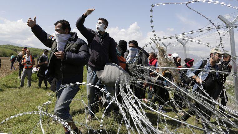 Vluchtelingen bij grens tussen Griekenland en Macedonië, ze hebben hun gezicht bedekt tegen de traangas. Beeld null
