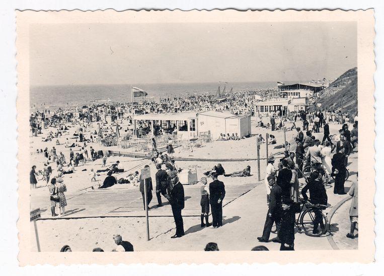 Een zomerse dag aan het strand in Zandvoort. Duitsers mengen zich onder de Nederlandse bevolking, maar voor Joden was geen plaats, getuige het bord linksonder. Beeld Collectie Gerard Groeneveld