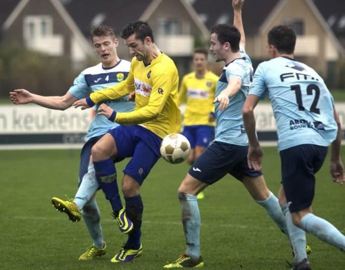 Dongen-speler Jaap van der Waarden werkt zich langs de verdediging van Halsteren in een competitieduel.