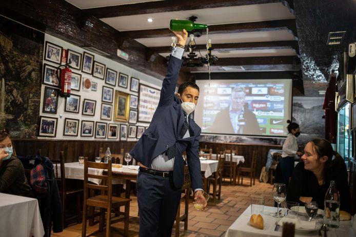 Een ober in restaurant El Ñeru schenkt een glas cider in.