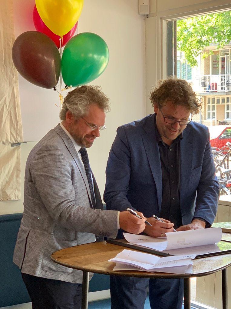 Chris Pettersson van Ymere en stadsdeelvoorzitter Maarten Poorter (rechts) ondertekenen een intentieovereenkomst voor investeringen in het winkelgebied van de Dapperbuurt. Beeld Ton Damen