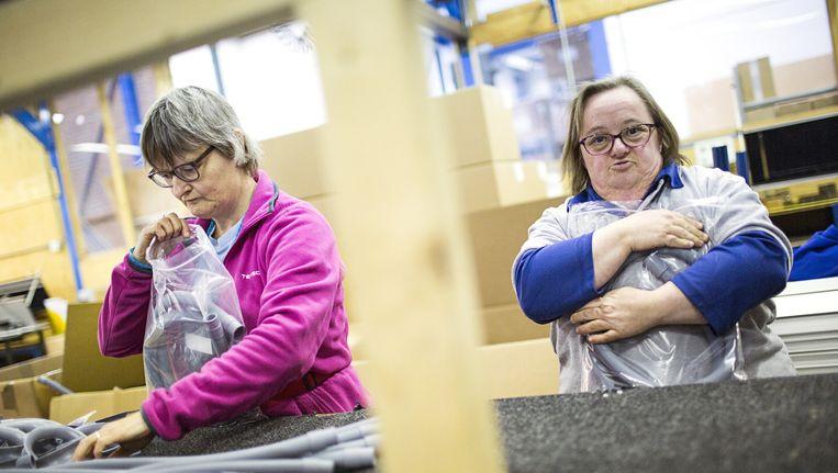 Twee werknemers van Nedco in Nieuwerkerk aan de IJssel, dat onder meer wasmachineslangen maakt. Beeld Julius Schrank