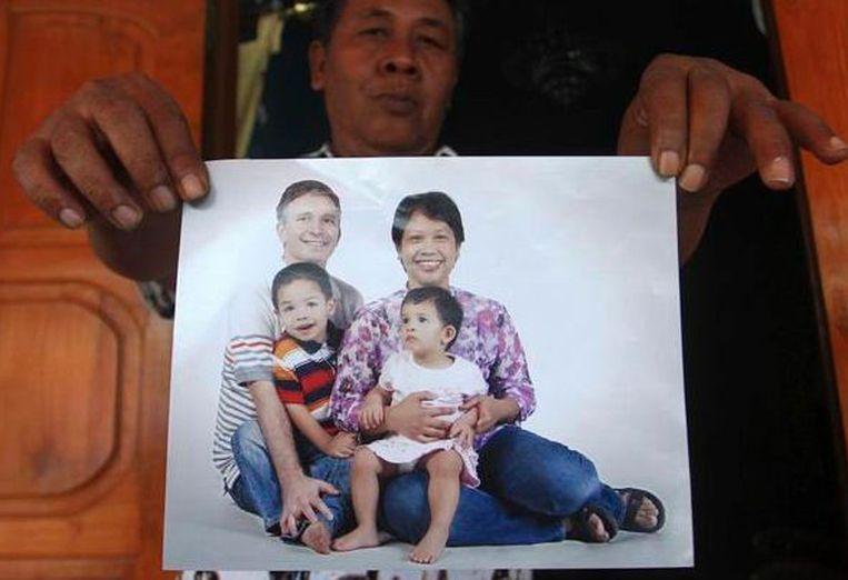 De broer van Yuli Hastini houdt een foto vast van zijn zus en haar gezin. Beeld AP