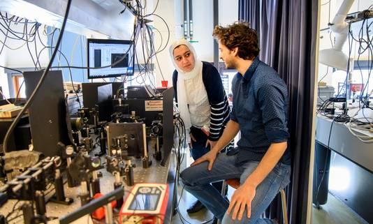 Onderzoekers Elham Fadaly en Alain Dijkstra bezig met een optisch opstelling om lichtemissie te meten.