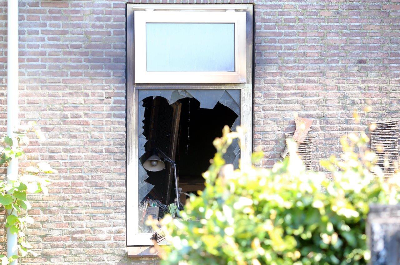 Brandweerlieden sloegen een raam kapot.