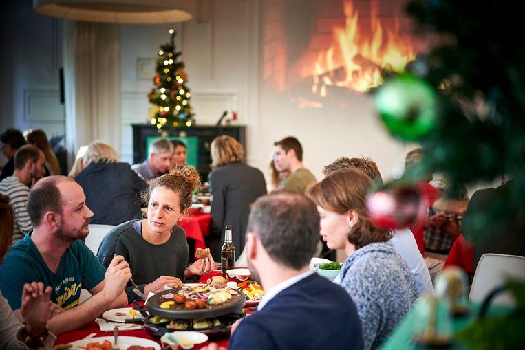 Alsof het echt Kerst is, aan een sissend gourmetstel, bakken linkse en rechtse Rotterdammers zij aan zij hun stukjes paprika en ananas. Beeld Phil Nijhuis
