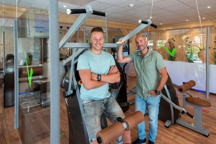 Zoon Bas en vader Wout ter Haar tussen de toestellen bij Slimmer Fit in Oosterbeek. Overal zijn spatschermen aangebracht.