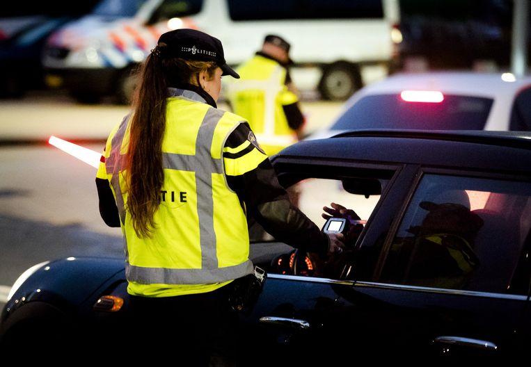 Een Nederlandse politieagent voert een alcoholcontrole uit tijdens een verkeerscontrole in Rotterdam, archiefbeeld ter illustratie.