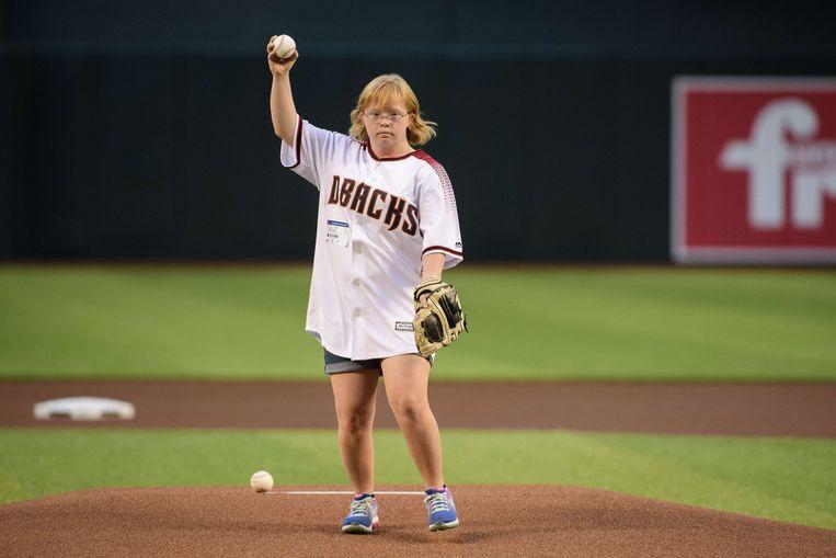 Amy Bockerstette (20) werpt de eerste bal in een honkbalwedstrijd in Phoenix. Zij  heeft het downsyndroom en de sport waarin ze echt uitblinkt is golf. Ze werd in één klap bekend toen ze begin dit jaar tijdens een oefenrondje  topgolfer Gary Woodland tegenkwam en voor zijn ogen en die van de camera's een fenomenale bal sloeg.  Beeld AFP