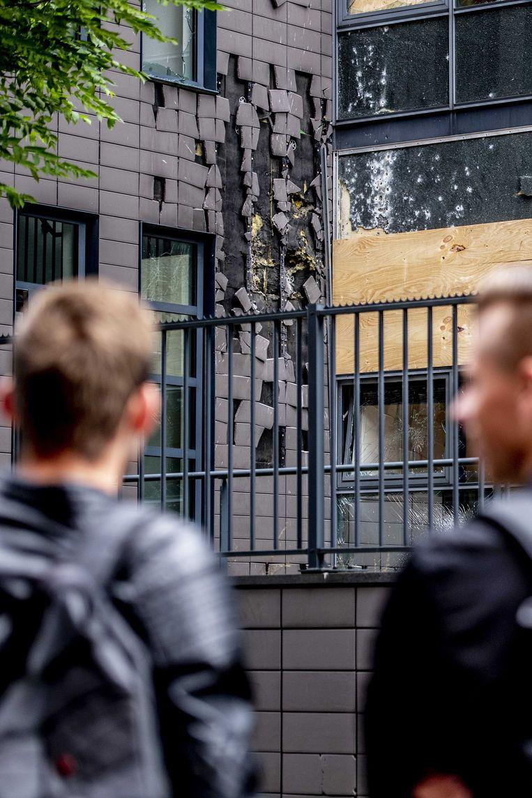 Voorbijgangers bekijken de plek waar een kantoorpand is beschoten met een antitankwapen.  Beeld ANP