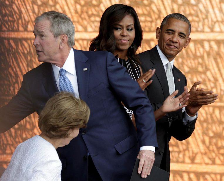 George W. Bush met de Obama's in september. Beeld Reuters